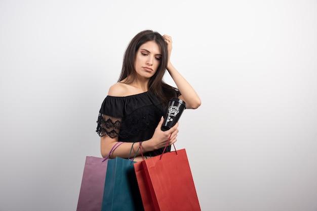 갈색 머리 여자 쇼핑백과 커피 컵과 함께 포즈.