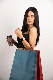 Donna castana in posa con borse della spesa e caffè. foto di alta qualità