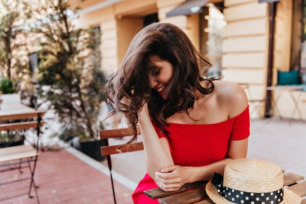 屋外レストランで恥ずかしがり屋の笑顔でポーズをとるブルネットの女性。帽子をかぶってテーブルに座っている陽気な白人の女の子の肖像画。
