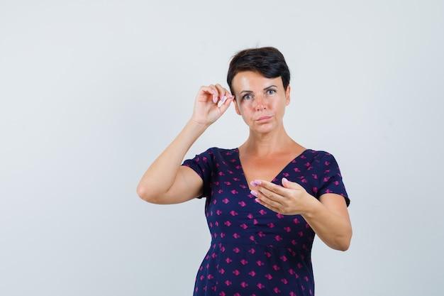 Donna castana che finge di strapparsi le sopracciglia, guardandosi allo specchio in abito fantasia viola e rosso e guardando concentrato. vista frontale.