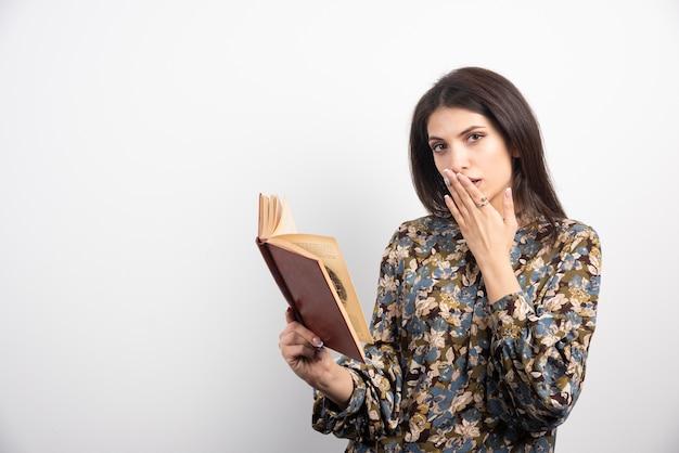 Libro di lettura della donna castana su una priorità bassa bianca.