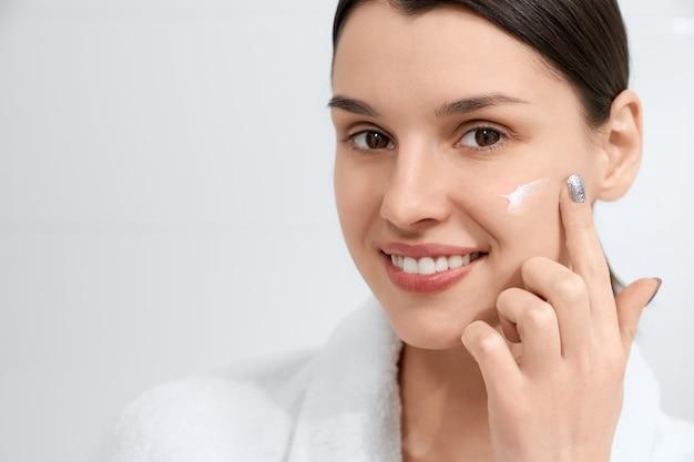 Donna castana in veste utilizzando crema per il viso a casa