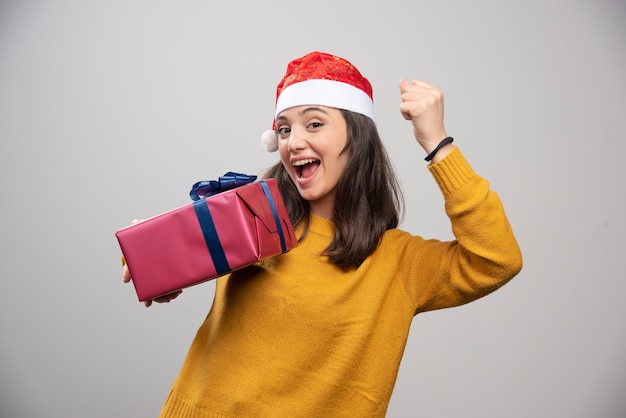Brunette woman in santa hat showing her fist and holding gift box.