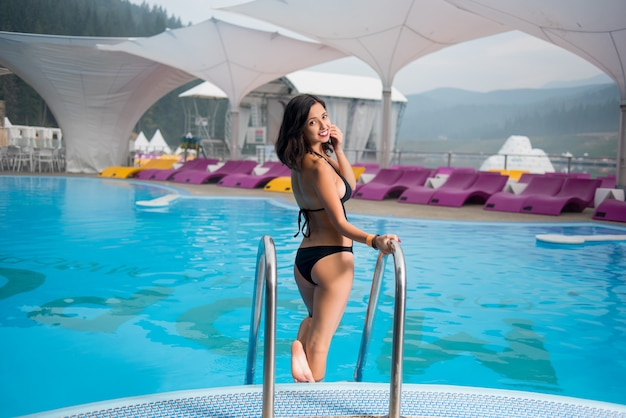 Brunette woman in a sexy black bikini near swimming pool and turning back to smile at the camera