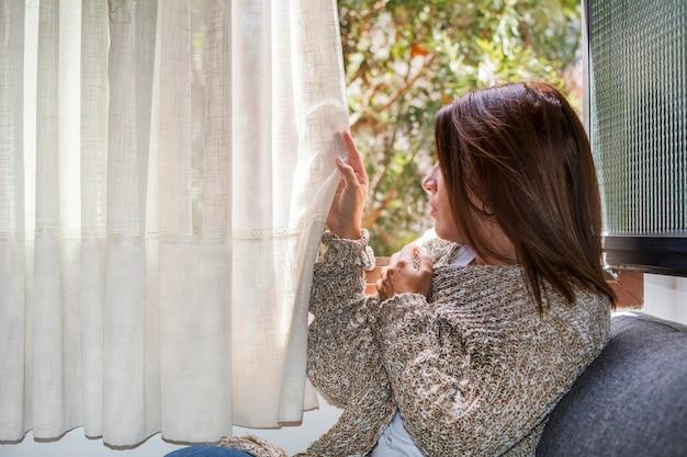 Брюнетка, укрытая от осеннего холода, убирает занавеску с окна, чтобы увидеть снаружи.