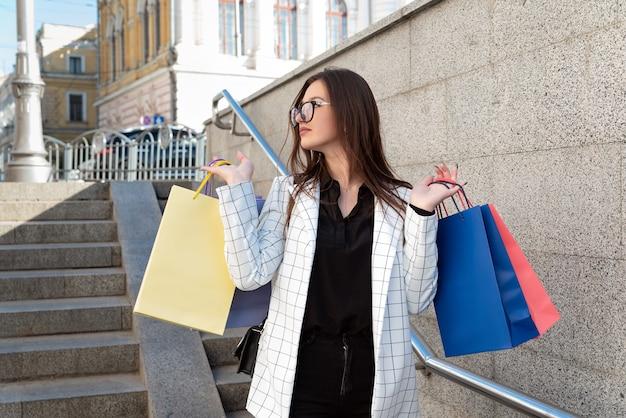 Покупки женщины брюнет. девушка держит разноцветные хозяйственные сумки на фоне города.