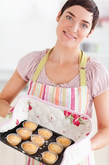 Brunette woman showing muffins