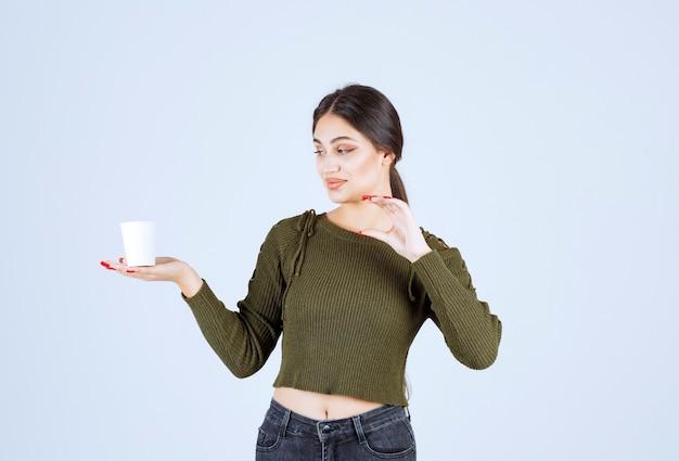 흰색 바탕에 플라스틱 컵을 보여주는 갈색 머리 여자.