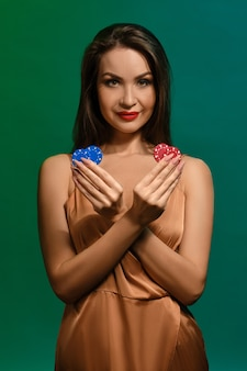Brunette woman in silk beige dress smiling showing four colorful chips in her crossed hands posing on green wall