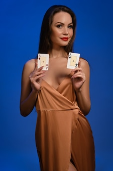 Brunette woman in silk golden dress she smiling showing two playing cards posing on blue wall