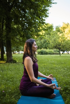 A brunette woman sits sideways and meditates on a yoga mat in nature