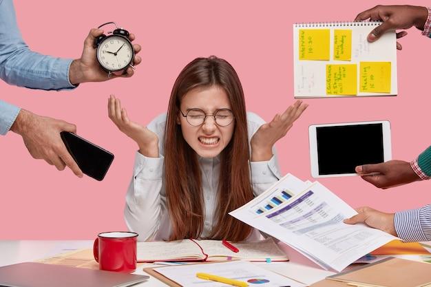 가제트와 서류로 둘러싸인 책상에 앉아 갈색 머리 여자