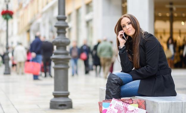 Brunette donna che si siede su una panchina e parlando al telefono