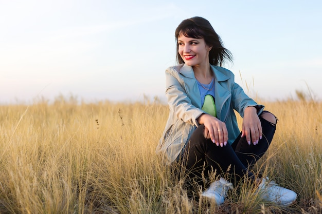 黄色の草原の草に座っているブルネットの女性