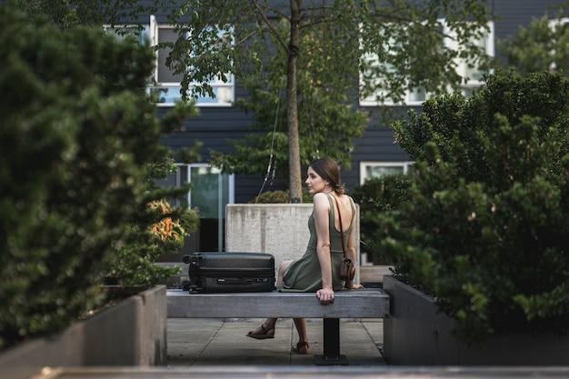 都市公園のセメント席に座っているブルネットの女性