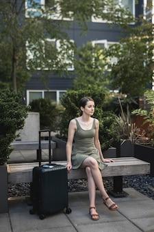 Брюнетка сидит на цементном сиденье с чемоданом