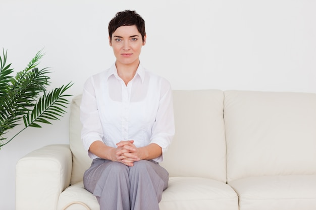 Brunette woman sitting on a sofa