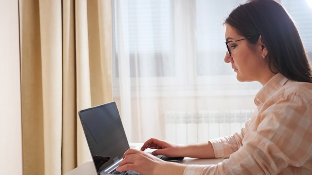 Brunette woman sitting at the table, typing on the laptop on the background of the window.