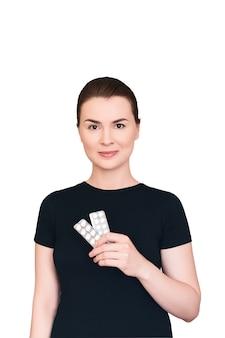 ブルネットの女性は微笑んで、白で隔離の丸薬で2つの水ぶくれを保持します治療の概念