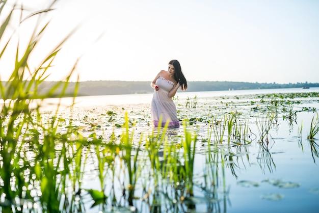 Брюнетка женщина улыбается и стоит в воде озера