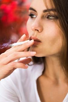 Brunette woman smokes a cigar