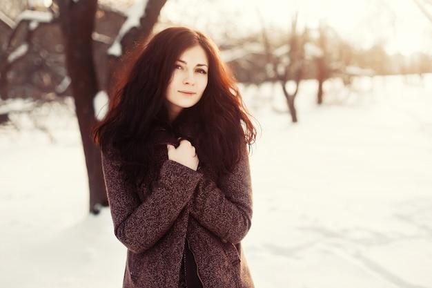 雪の中で立ってブルネットの女性
