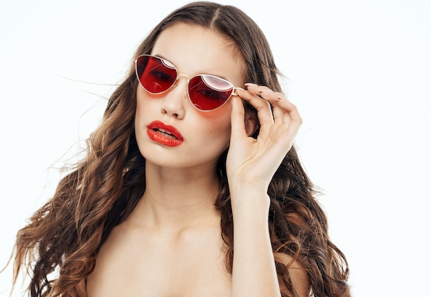 Brunette woman straightens glasses on her face and naked shoulders light background