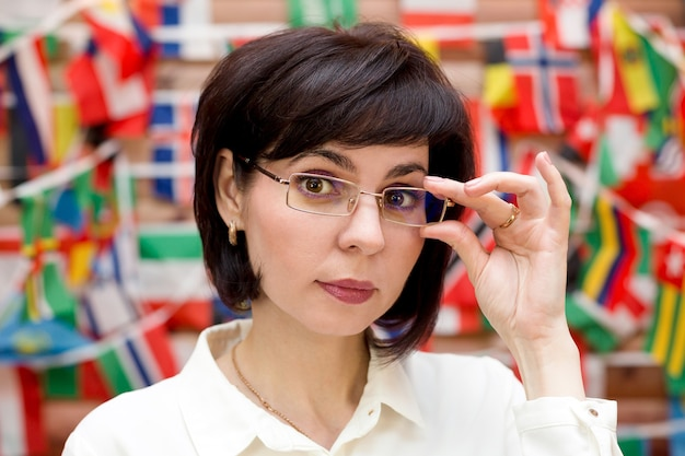 Brunette woman straightens glasses on her nose against the background of the flag of the states