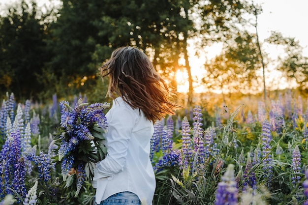 Brunette woman swirls holding lupines bouquet on a lawn on sunset