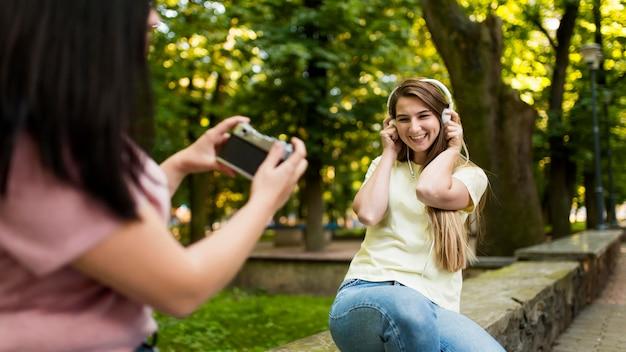 Брюнетка женщина фотографирует своего друга