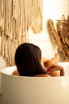 갈색 머리 여자 목욕 하 고 그녀의 다리를 터치. 그녀는 화장실에 앉아