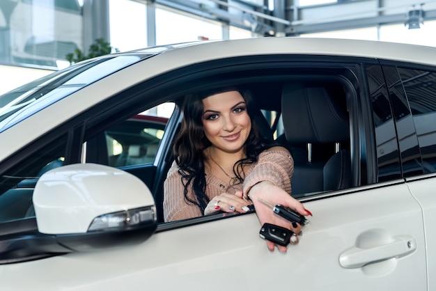 Brunette woman taking keys from new car