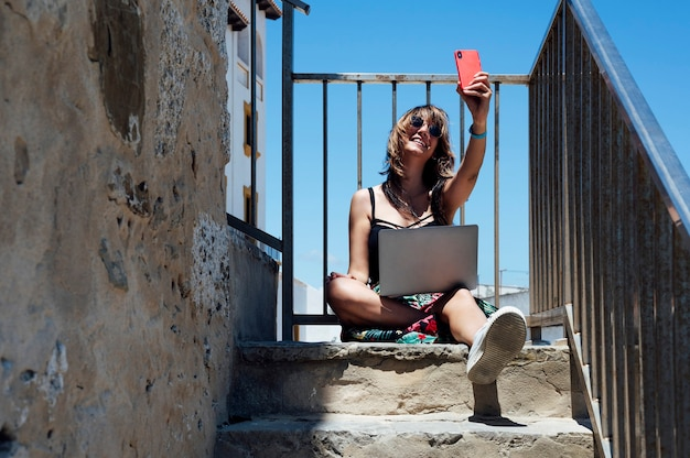 Brunette woman taking a selfie while working with laptop