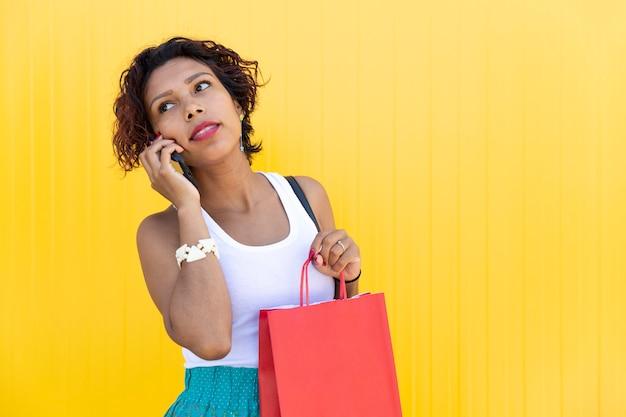 Брюнетка женщина разговаривает со своим смартфоном, держа ее хозяйственную сумку.