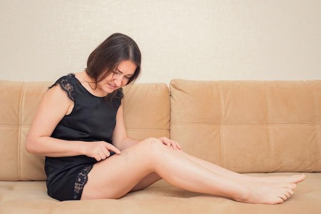 갈색 머리 여자는 소파 복사 공간에 앉아있는 동안 다리에 고통스러운 타박상을 만지고
