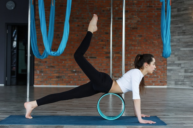 Brunette woman trains muscles on the stomach on a gymnastic circle