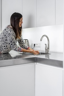 Brunette woman washing her hands after cooking on the kitchen