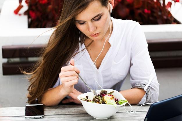 Брюнетка женщина смотрит что-то на планшете, сидя в ресторане