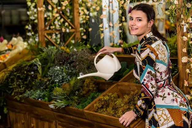 Brunette woman watering plant in green house