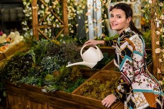 Брюнетка женщина полива растений в зеленом доме