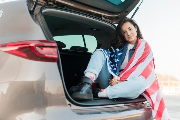 Брюнетка носить большой флаг сша в багажнике