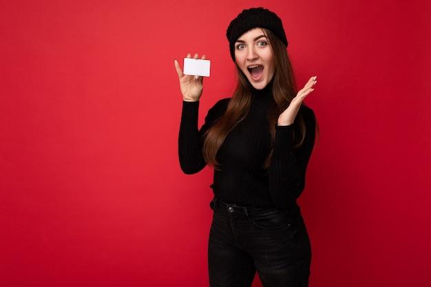 검은 스웨터와 모자를 입고 갈색 머리 여자는 카메라를보고 신용 카드를 들고 빨간색 배경에 고립.