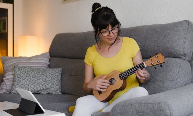 Brunette woman wearing glasses, with her hair tied back, learning to play the ukulele in online classes