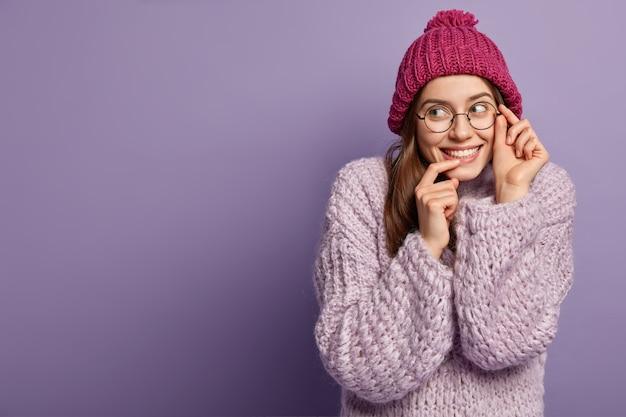 Donna castana che indossa cappello e maglione lavorato a maglia