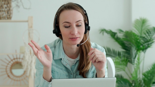 Brunette woman wears headset calling on laptop talks with online teacher studying, working from home