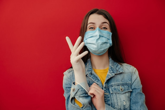 Brunette woman wears protective medical mask not to infect other people, puts on medical gloves, thinks about risk of epidemic disease, wears denim jacket, poses indoor against red background.