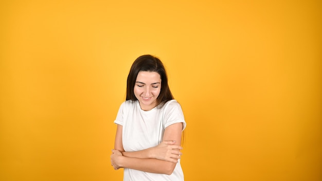 Brunette woman in white t-shirt hugging herself cross arms, feel cold chilly smiling kindly on yellow