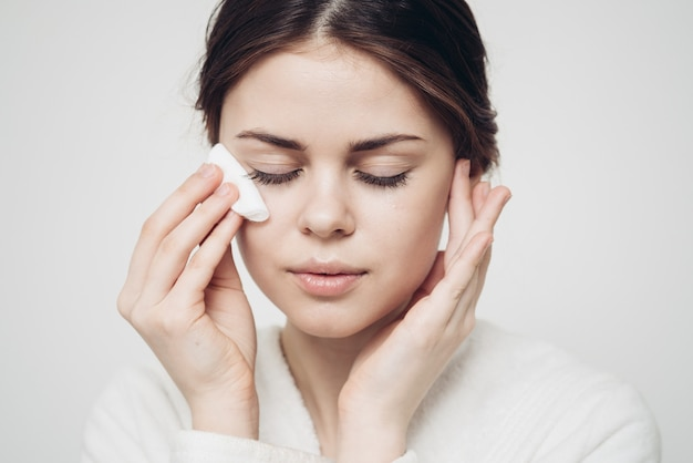 Brunette woman wipes her face with a white sponge on a light background