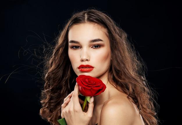 暗い背景のクローズアップで彼女の手に赤いバラを持つブルネットの女性