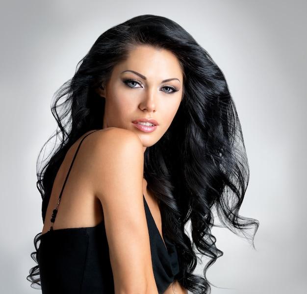 美しさの長い茶色の髪を持つブルネットの女性-灰色の背景のスタジオでポーズ
